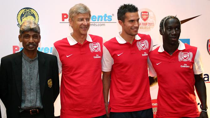 Arsenal manager Arsene Wenger, second from left, poses with his team players Robin van Persie, second from right, Bacary Sagna, right, and Malaysian national team coach K. Rajagopal after a press conference at a hotel in Kuala Lumpur, Malaysia, Monday, July 11, 2011. Arsenal Football Club will play with the Malaysia XI coached by Rajagopal in their friendly soccer match on Wednesday, July 13. (AP Photo/Lai Seng Sin)