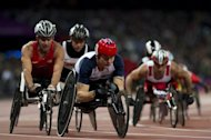 Britain's David Weir (C) competes in the men's 5,000m - T54 round 1 athletics track event during the London 2012 Paralympic Games at the Olympic Stadium in London on August 31. Packed crowds greeted the first day of athletics at the Paralympics but the jubilant mood was overshadowed by a mix-up that saw the wrong athlete awarded a gold