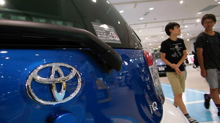 Visitors walks past a Toyota IQ compact car displayed at a Toyota showroom in Tokyo, Wednesday, July 30, 2014. Toyota remains No. 1 in global vehicles sales after the first six months of this year, followed by Volkswagen which bumped General Motors out of second place as the U.S. automaker grapples with a recall scandal. (AP Photo/Eugene Hoshiko)