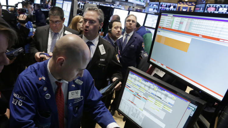 Specialist Mario Picone, left, works with traders at his post on the floor of the New York Stock Exchange Monday, March 25, 2013.  U.S. stock markets are opening higher after Cyprus clinched a last-minute bailout that saved it from bankruptcy. (AP Photo/Richard Drew)