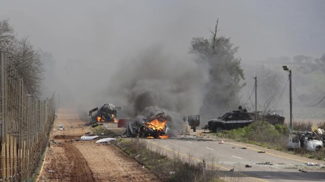 Burning vehicles are seen near the village of Ghajar on Israel's border with Lebanon