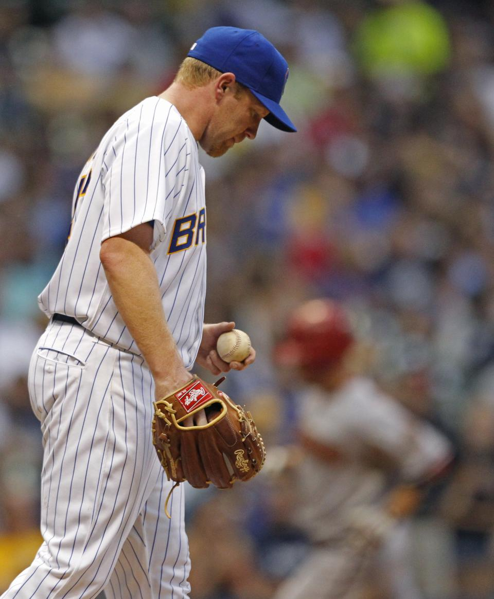 CORRECTS TO FOURTH INNING NOT THIRD INNING - Milwaukee Brewers starting pitcher Randy Wolf, left, looks down as Arizona Diamondbacks' Aaron Hill, right, rounds third base after hitting a two-run home run during the fourth inning of a baseball game on Friday, June 29, 2012, in Milwaukee. (AP Photo/Jeffrey Phelps)