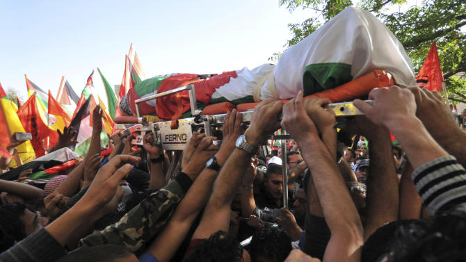Palestinians carry the body of Maysara Abu Hamdiyeh after it was released by the Israeli authorities near the settlement of Maaleh Adumim, West Bank, Wednesday, April 3, 2013. Abu Hamdiyeh, who had been serving a life sentence for his role in a foiled attempt to bomb a busy cafe in Jerusalem in 2002, died of cancer in an Israeli jail. (AP Photo/Mahmoud Illean)