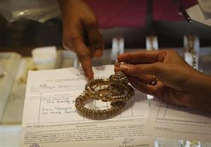 An employee explains the bill to a customer as gold bangles are placed on top of it inside a jewellery showroom in Mumbai August 30, 2013.