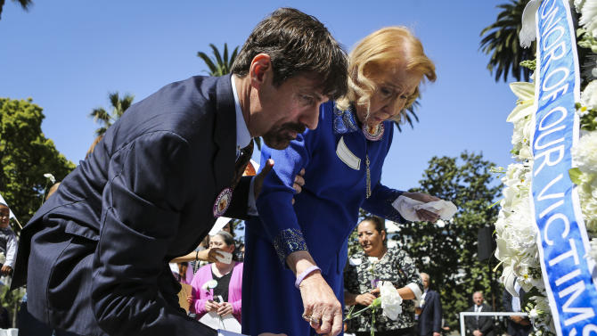 IMAGE DISTRIBUTED FOR MARSYSLAWFORALL.ORG - Dr. Henry T. Nicholas III, left, and his mother Marcella Leach lay a white carnation at the steps of the old Orange County Courthouse during the Orange County Victims' Rights March and Rally, Friday, April 26, 2013, in Santa Ana, Calif. Dr. Nicholas is co-founder of Broadcom Corp. and chief architect of Marsy's Law, www.marsyslawforall.org.  (Bret Hartman/AP Images for MarsysLawForAll.org)