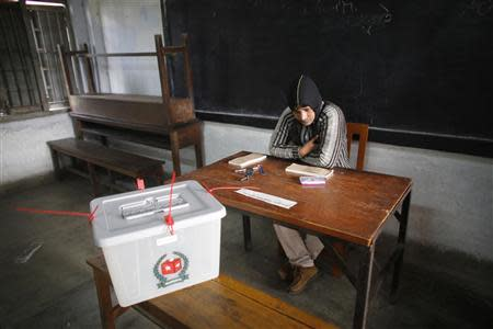 A polling officer works at an empty station during parliamentary elections in Dhaka