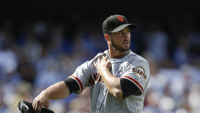 San Francisco Giants' George Kontos looks at the scoreboard as he walks off the field during the eighth inning of a season-opening baseball game against the Los Angeles Dodgers in Los Angeles, Monday, April 1, 2013. (AP Photo/Jae C. Hong)