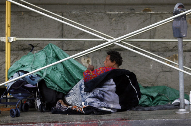 FILE- In this April 14, 2006, file photo, a homeless woman seeks shelter under construction scaffolding in the Skid Row area of downtown Los Angeles. The city of Los Angeles is violating the county he