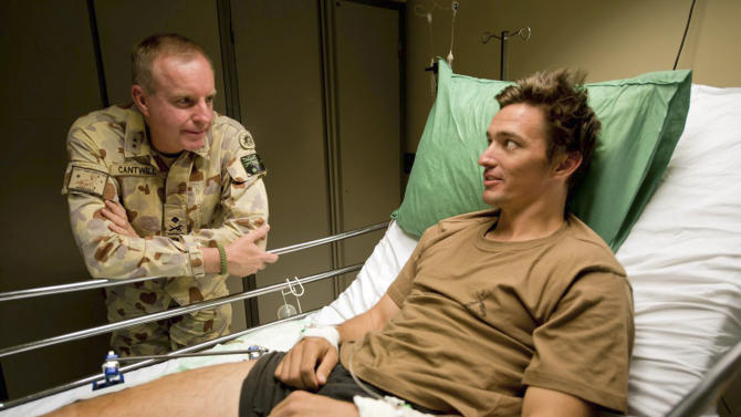 """In this undated photo provided by Maj. Gen. John Cantwell, left, the general talks with an unidentified injured man at an undisclosed location in Afghanistan. Cantwell could see the ridges and calluses of the skin, and the pile of desert sand that had swallowed the rest of the Iraqi soldier. The troops Cantwell was fighting alongside in the Gulf War had used bulldozing tanks to bury the man alive. This hand - so jarringly human amid the cold mechanics of bombs and anonymous enemies - was about to wedge itself, the Australian man would write decades later, """"like a splinter under the skin of my soul."""" It would lead, along with other battlefield horrors, to the splintering of his mind and to a locked psychiatric ward. (AP Photo/Maj. Gen. John Cantwell, Sergeant Neil Ruskin) EDITORIAL USE ONLY"""