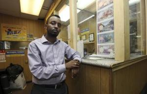 Hussein stands at the counter of his money transfer business Mustaqbal Express in Minneapolis