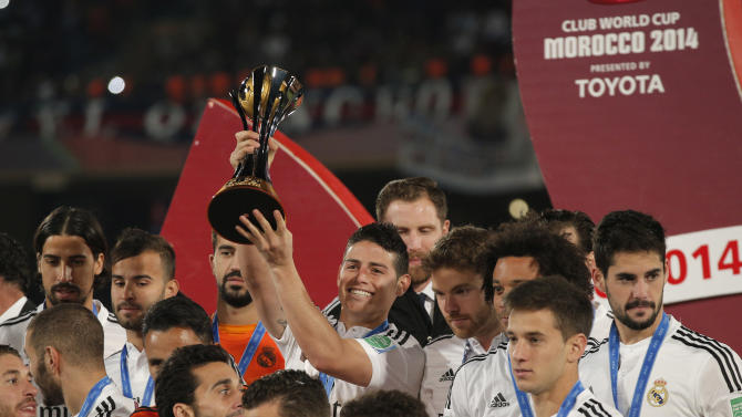 Real Madrid's James Rodriguez, centre, poses with the trophy alongside team mates after winning the final soccer match between Real Madrid and San Lorenzo at the Club World Cup soccer tournament in Marrakech, Morocco, Saturday, Dec. 20, 2014. (AP Photo/Christophe Ena)