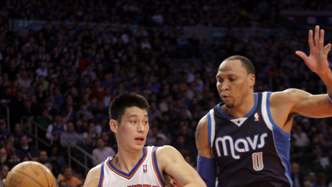 New York Knicks' Jeremy Lin, left, passes around Dallas Mavericks' Shawn Marion during the first half of an NBA basketball game in New York, Sunday, Feb. 19, 2012. The Knicks defeated the Mavericks 104-97. (AP Photo/Seth Wenig)