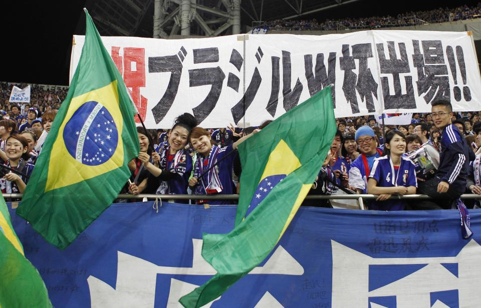 Japan's supporters celebrate after their team's game against Australia during their Asian zone Group B qualifying soccer match for the 2014 World Cup at Saitama Stadium in Saitama, near Tokyo, Tuesday, June 4, 2013. (AP Photo/Koji Sasahara)
