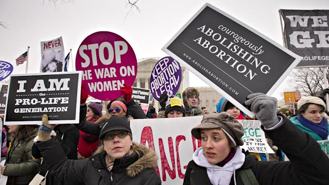 Anti-abortion activists and supporters of legal abortion stand in front of the Supreme Court in Washington, Friday, Jan. 25, 2013, on the 40th anniversary of the Roe v. Wade decision.  Thousands of anti-abortion demonstrators marched through Washington to the steps of the U.S. Supreme Court to protest the landmark decision that legalized abortion. (AP Photo/J. Scott Applewhite)