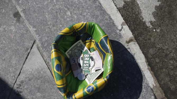 A soccer ball designed with Brazil's national colors, formed by a street performer into a receptacle to collect tips left by tourists, sits in front of the Maracana Stadium, in Rio de Janeiro, Brazil, Wednesday, May 27, 2015. Brazilian Jose Maria Marin, the former president of the Brazilian Football Confederation, was among seven high-ranking soccer officials arrested Wednesday in Zurich on U.S. charges of corruption. (AP Photo/Silvia Izquierdo)