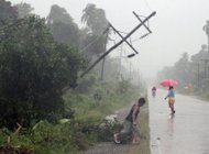 Residents brave heavy rains next to an electric post after Typhoon Bophal hit the city of Tagum, Davao del Norter province, on the southern island of Mindanao on December 4, 2012. There were 49 fatalities in a mudslide in the mountainous town of New Bataan alone, and another 33 died in rural settlements elsewhere in Mindanao.