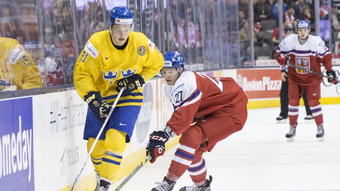 Sweden's William Nylander, left, brings the puck past Czech Republic's Dominik Masin in third-period preliminary-round hockey game action at the IIHF World Junior Championship in Toronto, Friday, Dec. 26, 2014. (AP Photo/The Canadian Press, Chris Young)