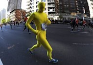 This file photo shows runners making their way up 1st Avenue in Manhattan during the 2011 ING New York City Marathon, last November. N.Y. City Marathon organizers continued to plan for Sunday&#39;s race as the metropolis coped with the chaotic aftermath of deadly superstorm Sandy