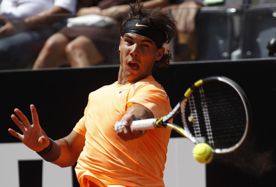Spain's Rafael Nadal returns the ball to Tomas Berdych, of Czech Republic, during their quarter final match at the Italian Open tennis tournament, in Rome, Friday, May 18, 2012. (AP Photo/Alessandra Tarantino)