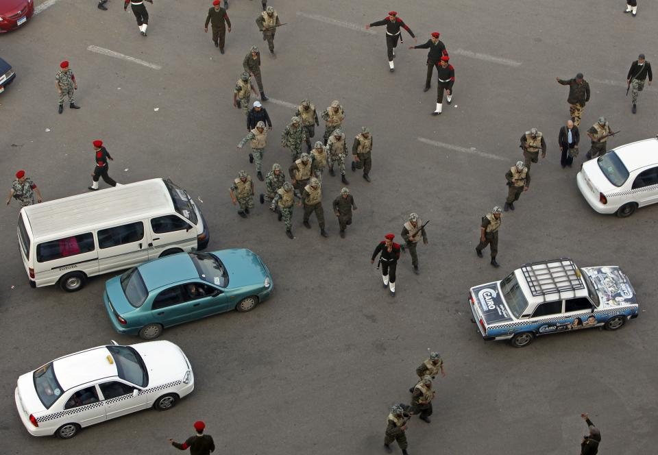 Military police and soldiers walk among traffic as they clear remaining protestors inTahir square in Cairo, Egypt, Monday Feb. 14, 2011. Egypt's military rulers dissolved parliament Sunday, suspending the constitution and promising elections in moves cautiously welcomed by pro-democracy protesters.(AP Photo/Hussein Malla)