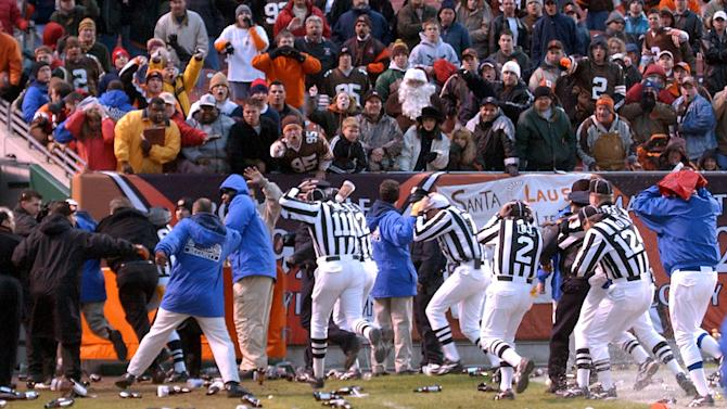 FILE - In this Dec. 16, 2001, file photo, officials cover their heads as they leave the field amid debris thrown by fans after an NFL football game between the Cleveland Browns and the Jacksonville Jaguars was stopped with 48 seconds left on the clock in Cleveland. The game was stopped for about a half-hour because of the violence. (AP Photo/The Repository, Scott Heckel, File) MANDATORY CREDIT