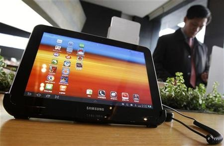 A visitor looks around behind Samsung Electronics' Galaxy Tab 10.1 tablet displayed for customers at a registration desk at KT's headquarters in Seoul