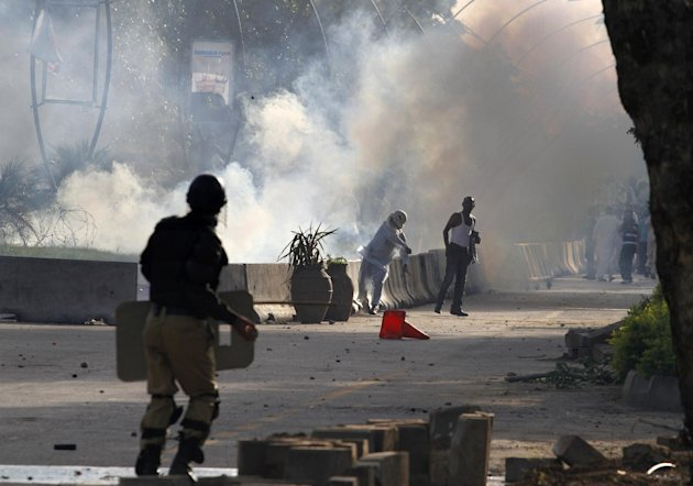 A Pakistani protestor hurls back a tear gas canister fired by police during clashes that erupted as protestors tried to approach the U.S. embassy, Friday, Sept. 21, 2012 in Islamabad, Pakistan. Protes