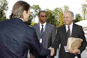French Finance Minister Baroin shakes hands with socialist party member Fabius at the MEDEF union summer forum in Jouy-en-Josas