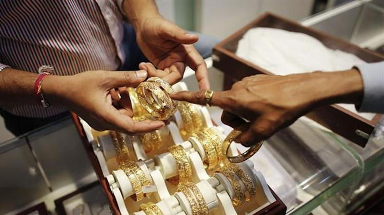 An employee shows gold bangles to a customer at a jewellery showroom in Mumbai November 1, 2013. REUTERS/Danish Siddiqui/Files