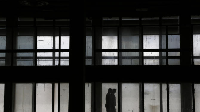 In this Tuesday, Nov. 25, 2014 photo, the ghost-like silhouettes of United Nations peacekeepers walking past the grimy windows of the departure lounge of the long-abandoned Nicosia airport that lies inside a United Nations-controlled buffer zone separating the breakaway Turkish speaking north of ethnically divided Cyprus from the internationally recognized Greek speaking south. Once an emblem of the young republic's growing confidence just 14 years after independence from British colonial rule, the airport overnight became a symbol of a future hijacked by unresolved conflict. (AP Photo/Petros Karadjias)