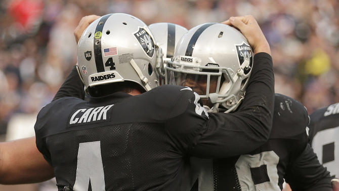 Oakland Raiders running back Jamize Olawale, right, and quarterback Derek Carr (4) celebrate after connecting on a 1-yard touchdown reception against the Buffalo Bills during the fourth quarter of an NFL football game in Oakland, Calif., Sunday, Dec. 21, 2014. (AP Photo/Ben Margot)