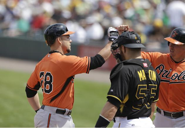 Baltimore Orioles' Steve Pearce, left, receives a high-five at the plate in front of Pittsburgh Pirates catcher Russell Martin, after hitting a two-run homerun during the fourth inning of a spring