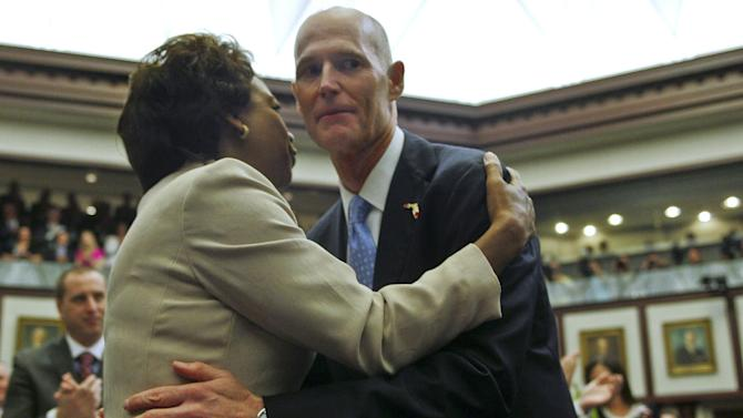 In this Tuesday, March 5, 2013 file photo, Florida Lt. Gov. Jennifer Carroll and Gov. Rick Scott embrace prior to his State of the State speech in the Florida House of Representatives in Tallahassee, Fla.  Carroll resigned and nearly 60 other people were charged in a widening scandal of a purported veterans charity that authorities said Wednesday, March 13, 2013 was a $300 million front for illegal gambling. (AP Photo/Phil Sears, File)