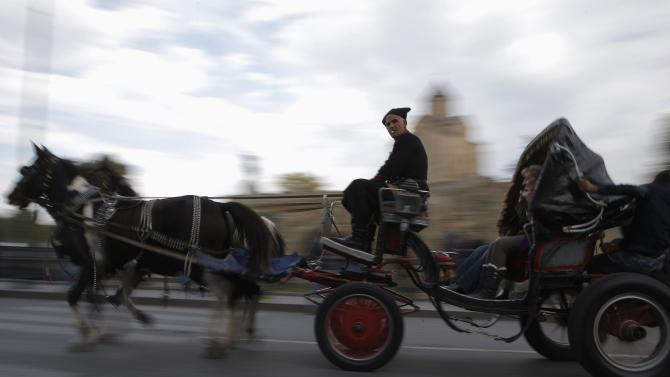 People ride in a horse carriage during the annual Tbilisoba festival, celebrating Tbilisi City Day, in the Georgian capital Tbilisi