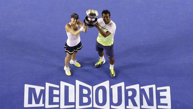 Martina Hingis of Switzerland, left,  and Leander Paes of India hold up the trophy after defeating Kristina Mladenovic of France and Daniel Nestor of Canada in the mixed doubles final at the Australian Open tennis championship in Melbourne, Australia, Sunday, Feb. 1, 2015. (AP Photo/Lee Jin-man)