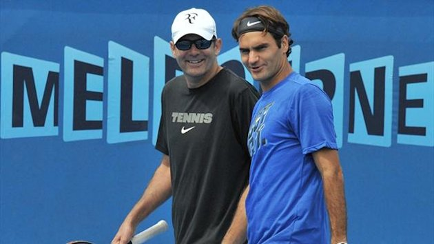 Roger Federer chats with one of his support crew during a practice session for the upcoming Australian Open in Melbourne (AFP)