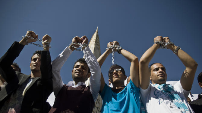 Yemeni men chain themselves to look handcuffed to protest against the Shiite insurgency during a rally in Sanaa, Yemen, Saturday, Nov. 22, 2014. (AP Photo/Hani Mohammed)
