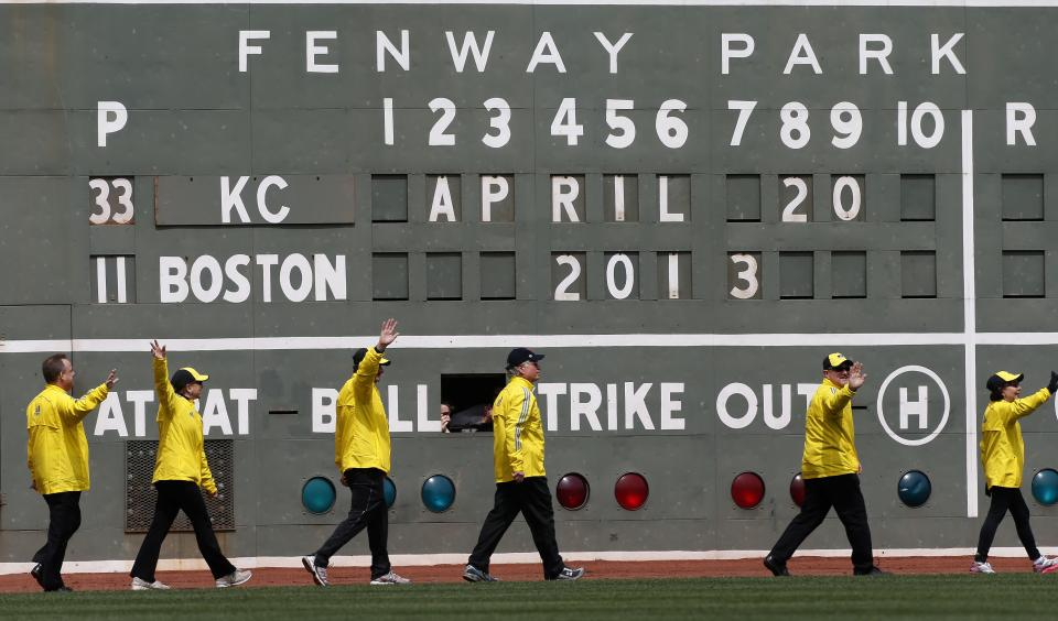 Boston Marathon volunteer workers walk onto the field before a baseball game between the Boston Red Sox and the Kansas City Royals in Boston, Saturday, April 20, 2013. (AP Photo/Michael Dwyer)
