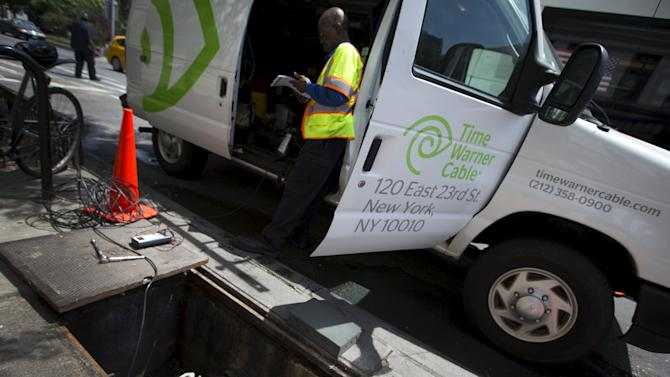 A Time Warner Cable service technician works on cable service from a van parked on the Upper West side of the Manhattan borough of New York City