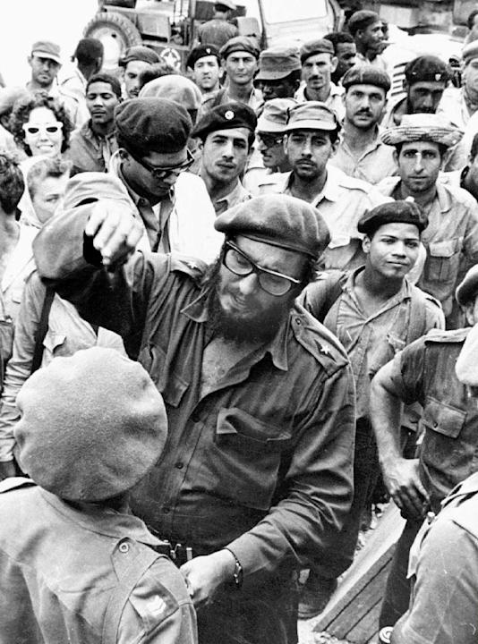 This April 1961 file photo shows Fidel Castro, center, with members of the Revolutionary Armed Forces at his base of operations at the Australia Sugar Refinery in Jaguey, near Playa Giron, during the