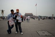 Official tourist photographers stand on Tiananmen Square in Beijing, on June 4, 2013. Tens of thousands of Hong Kongers have braved thunder and a torrential downpour to attend a candlelight vigil marking the 24th anniversary of China's bloody Tiananmen crackdown, as Beijing blocked commemoration attempts
