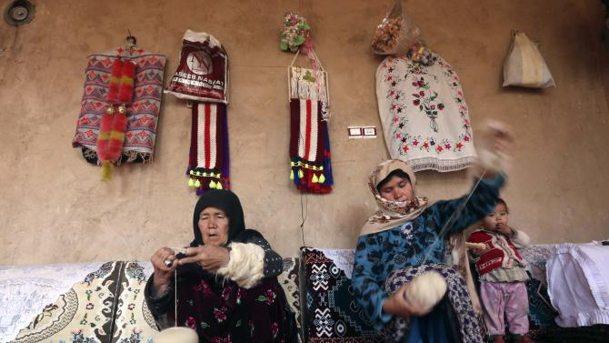 Afghan women spin wool into yarn, used to weave carpets, in Herat