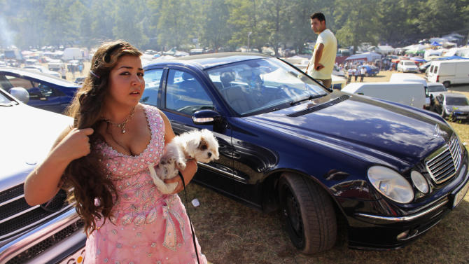 A Roma girl holds her pet dog during the traditional ethnic Roma festival in Costesti
