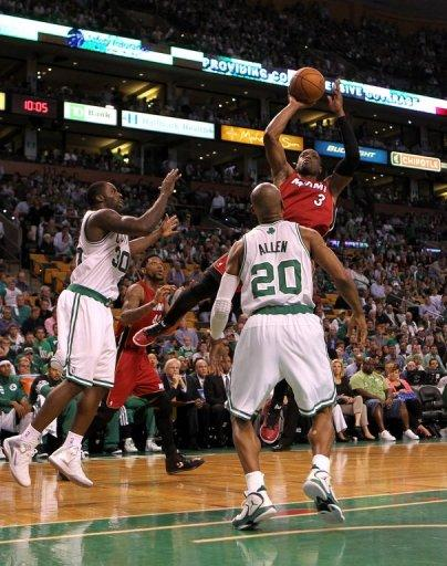 Dwyane Wade of the Miami Heat attempts a shot against Brandon Bass (L) and Ray Allen of the Boston Celtics