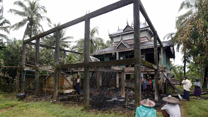 In this photo taken on Thursday, Oct. 3, 2013, Muslim men sit near a mosque destroyed in an attack by Buddhists in Thabyuchaing village, Thandwe township, Rakhine State, in western Myanmar. Even as President Thein Sein came to western Myanmar to urge an end to sectarian violence, security forces could not prevent Buddhist mobs from torching the homes of minority Muslims or hacking them to death, at times, unwittingly, even encouraging them. That has raised questions about the government's ability to quench a virulent strain of religious hatred blamed for the deaths of more than 240 people in the last 18 months. The latest attack occurred Tuesday, Oct. 1, in Thandwe township, killing five just hours before President Thein touched down for a scheduled visit. (AP Photo/Khin Maung Win)
