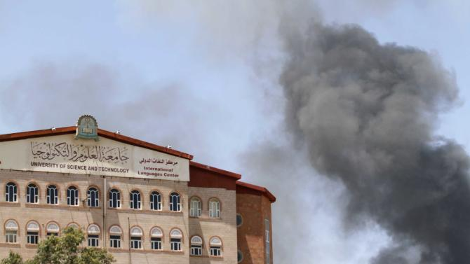 Smoke rises from the main gate of the army's first armoured division near the building of the University of Science and Technology, which is under attack from Shi'ite Houthi militants, in Sanaa