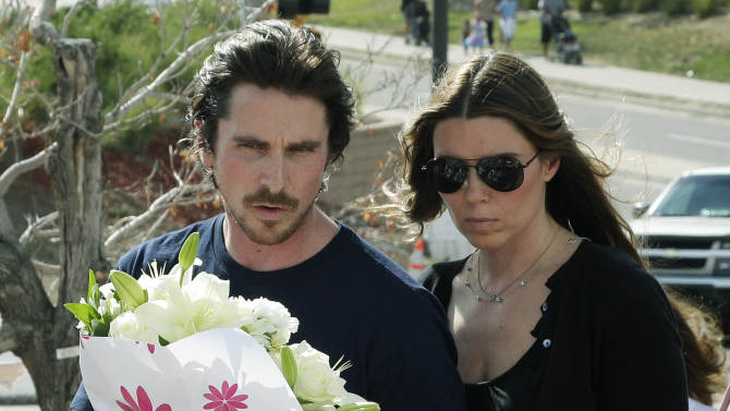 "Actor Christian Bale and his wife Sibi Blazic carry flowers to place on a memorial to the victims of Friday's mass shooting, Tuesday, July 24, 2012, in Aurora, Colo. Twelve people were killed when a gunman opened fire during a late-night showing of the movie ""The Dark Knight Rises,"" which stars Bale as Batman. (AP Photo/Ted S. Warren)"