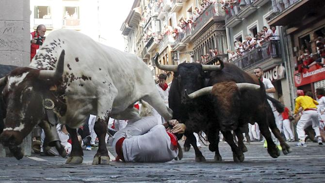 A steer jumps over a fallen runner as two Jandilla fighting bulls follow behind at the Mercaderes curve during the first running of the bulls of the San Fermin festival in Pamplona