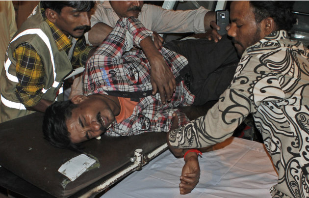 A Pakistani man, who was injured in a bomb blast, is brought to a hospital in Karachi, Pakistan, Sunday, March 3, 2013. Pakistani officials say a bomb blast has killed dozens of people in a neighborho