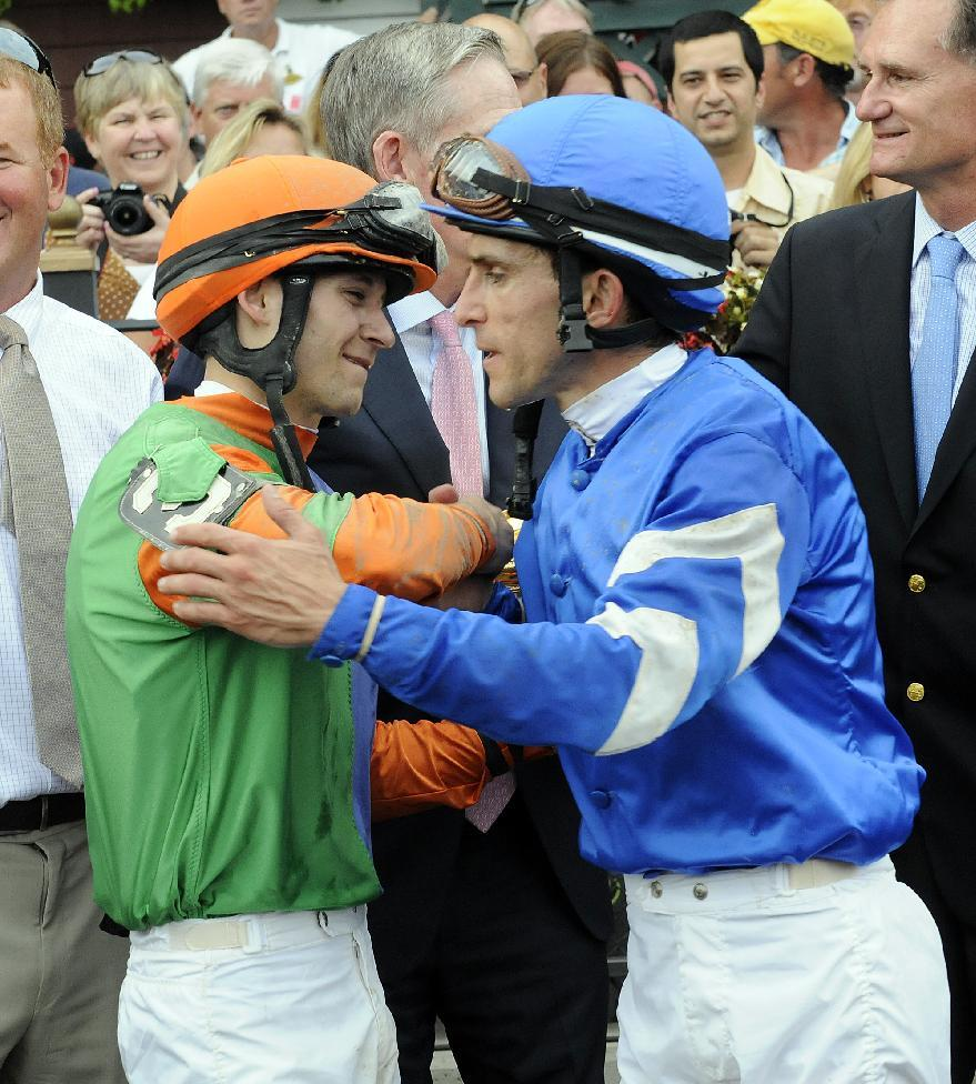 Jockeys David Cohen, left, who rode Golden Ticket, and Ramon Dominguez, who rode Alpha, celebrate in the winner's circle after a dead heat in the Travers Stakes horse race at Saratoga Race Course in Saratoga Springs, N.Y., Saturday, Aug. 25, 2012. (AP Photo/Hans Pennink)